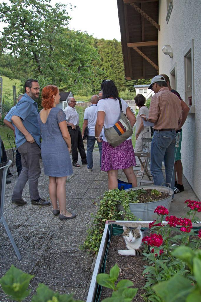 集会の前におしゃべりをする村人たち。花壇に立つ家主もくつろいだ様子
