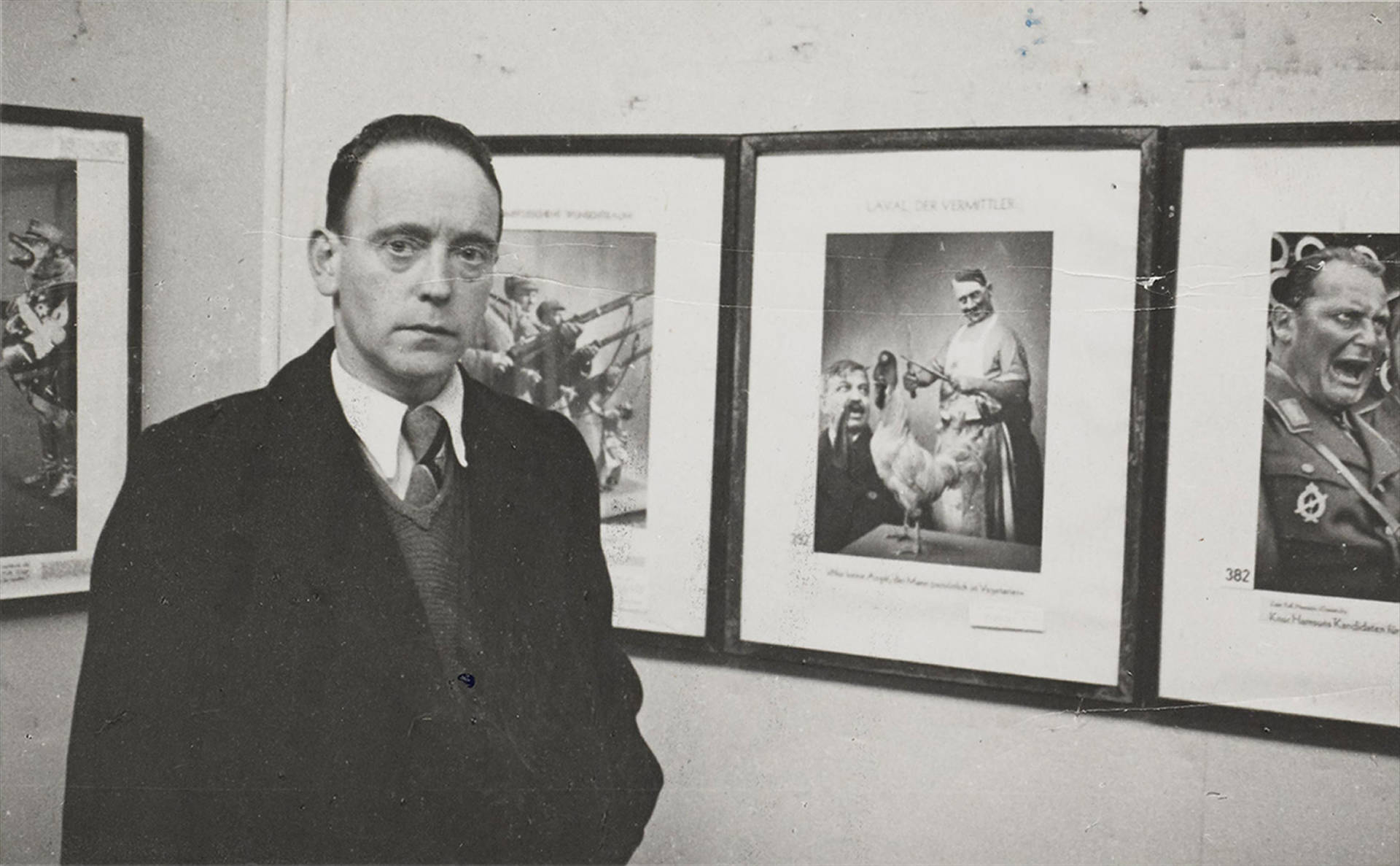 John Heartfield in front of his works of art at the Mánes Art Association, Prague, 1936