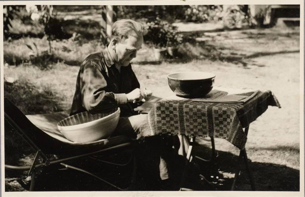 John Heartfield outdoors preparing food in Waldsieversdorf, mid-1960s