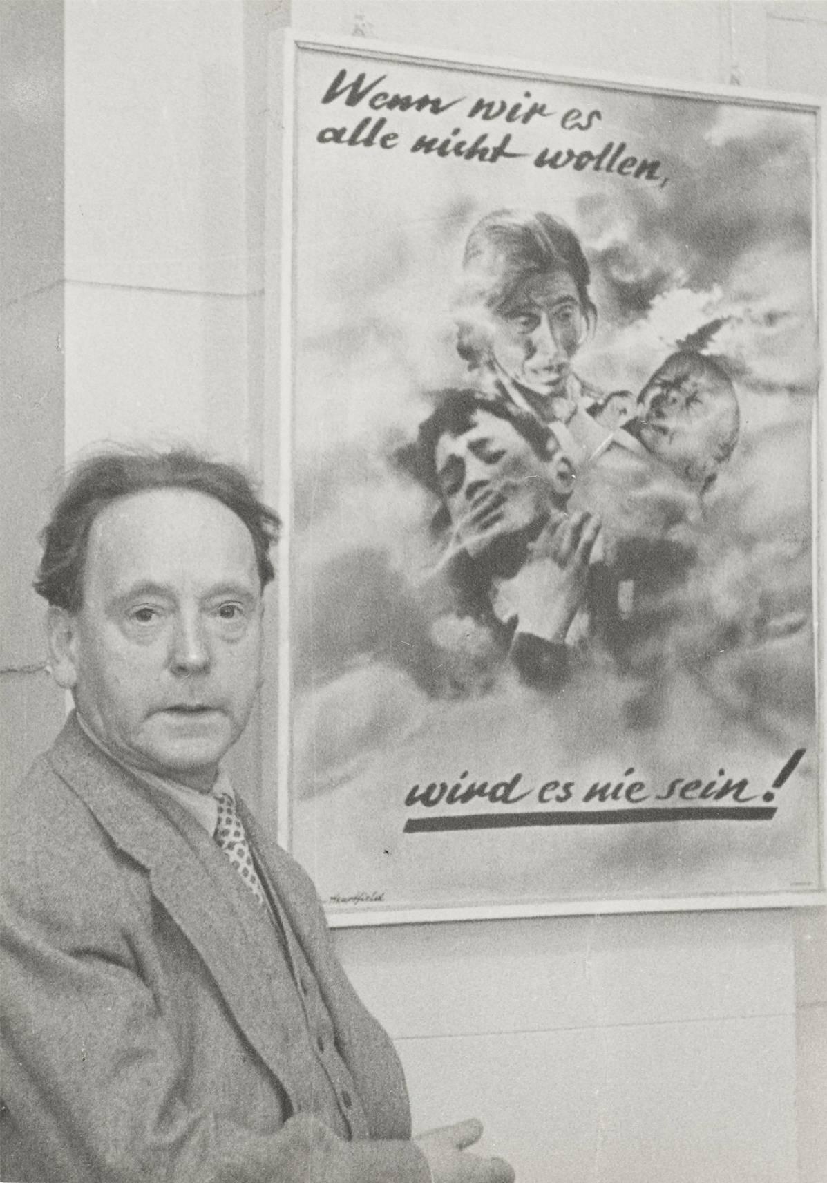 """John Heartfield in seiner Ausstellung """"John Heartfield und die Kunst der Fotomontage"""", im Hintergrund sein Werk """"Wenn wir es alle nicht wollen, wird es nie sein!"""", Berlin, 1957"""