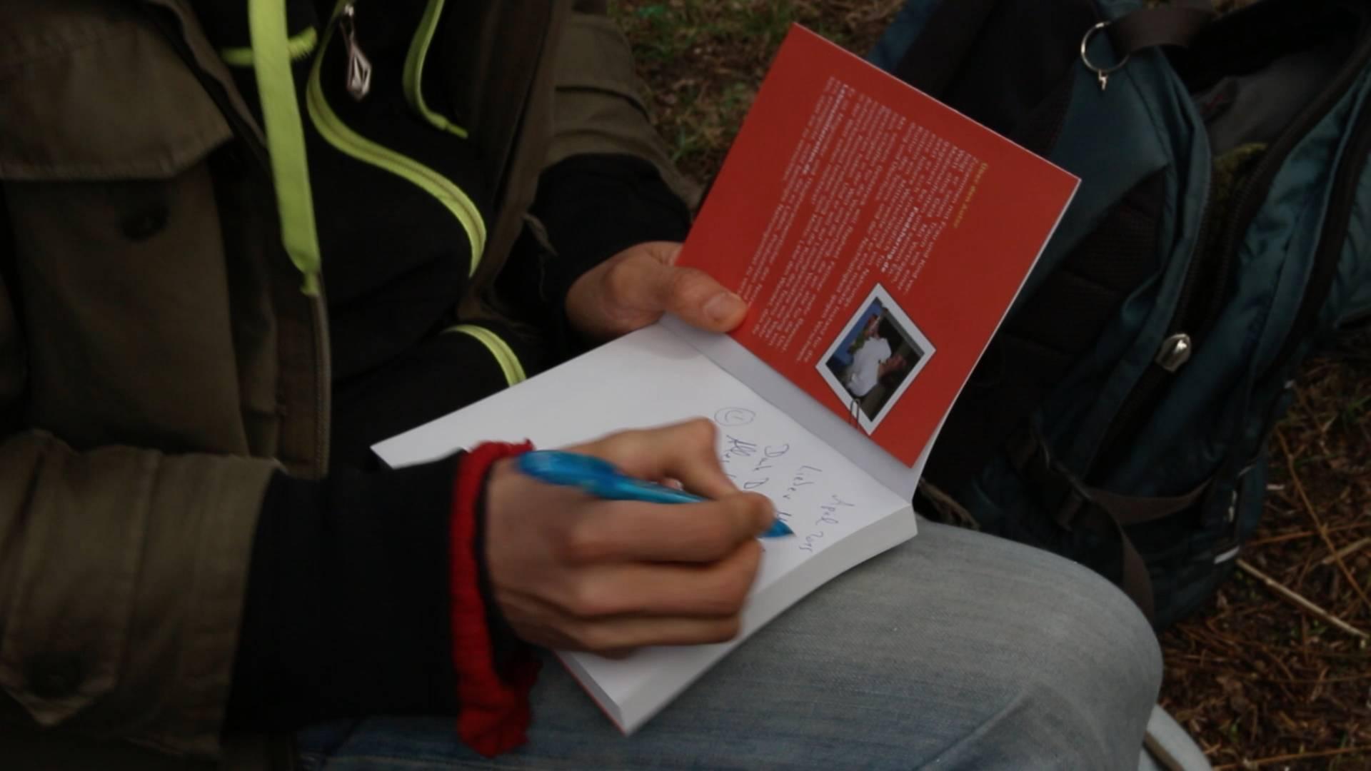 """Raphael beim Signieren seines Buches: """"Glücklich ohne Geld"""""""