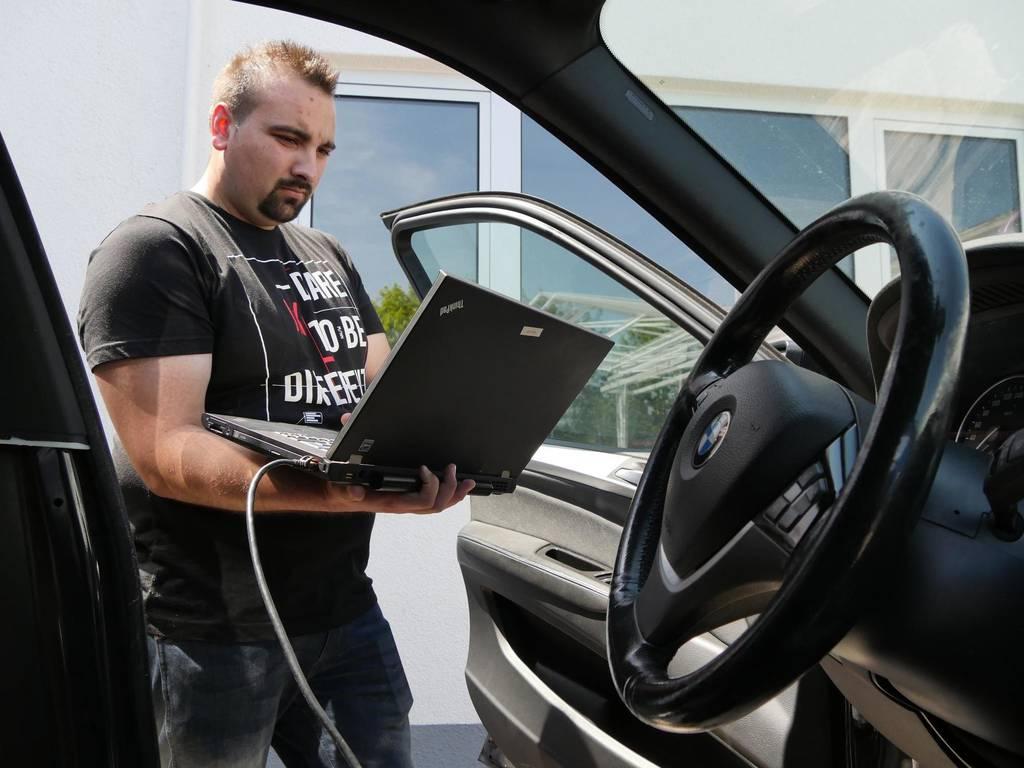 Wo liegt das Problem? Fachinformatiker Paul Doliwa überprüft mit einem Laptop ein defektes Auto.